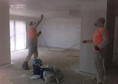 Team members doing internal spray painting of a new house